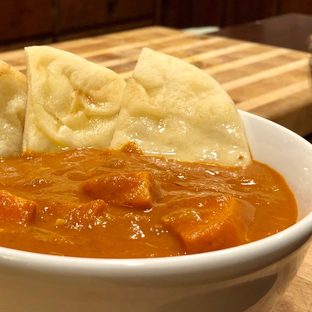 Sweet Potato Tikka Masala in a bowl with pieces of naan arranged around the side