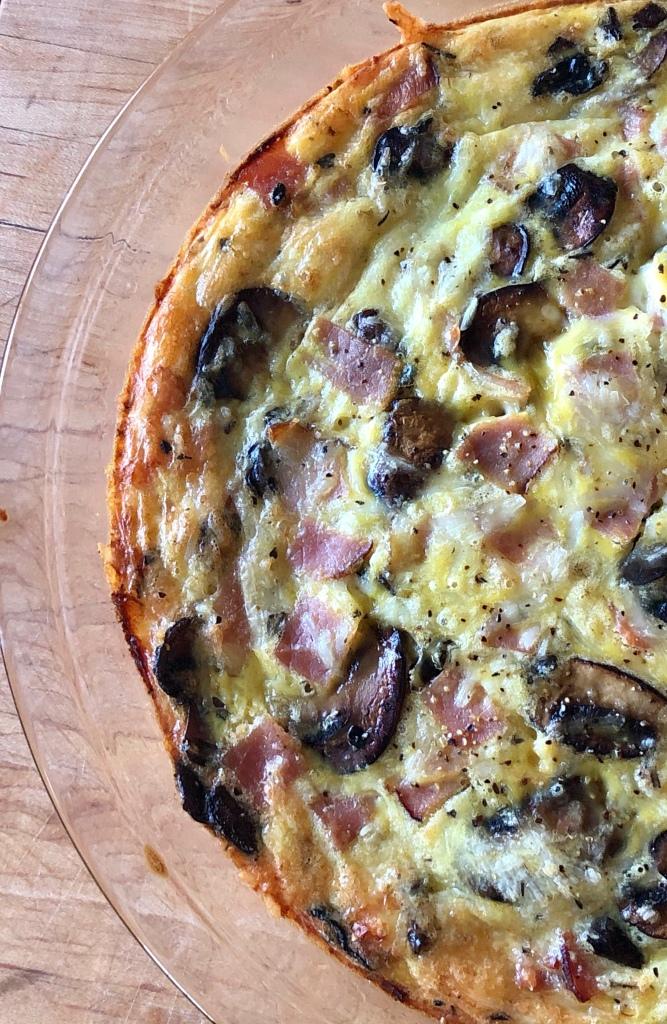 Closeup of Mushroom, Ham, and Swiss Crustless Quiche in a glass pie plate