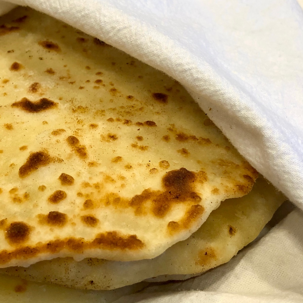 Several pieces of Quick Yogurt Flatbread wrapped in a tea towel