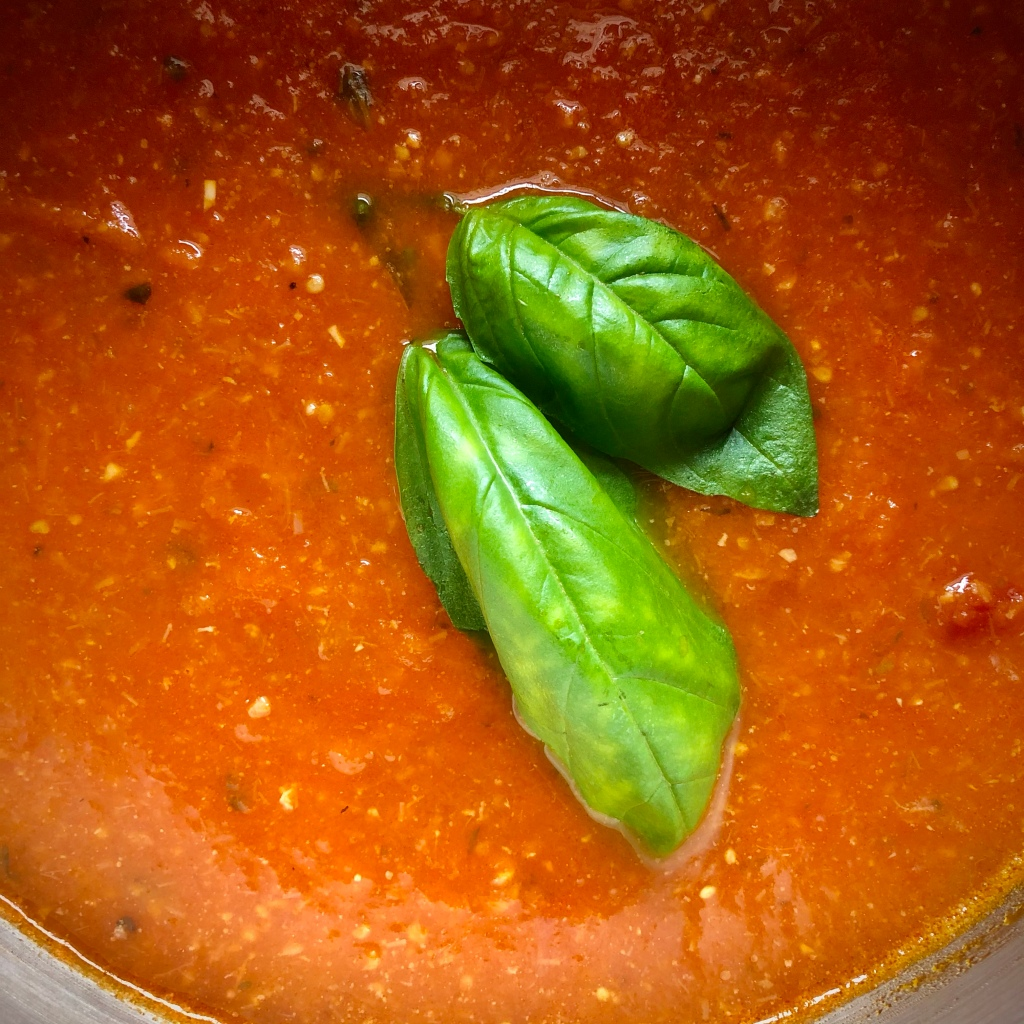 Basil-Bacon Tomato Soup in a stockpot, topped with two fresh basil leaves