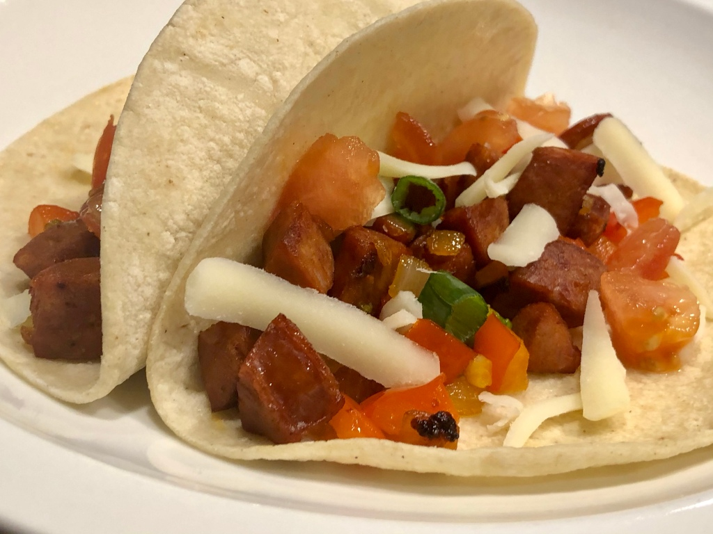 Two corn tortillas arranged as tacos; the focus is on one taco, with a mixture of diced sausage, peppers, onions, tomatoes , green onions, and sprinkled with shredded white cheese