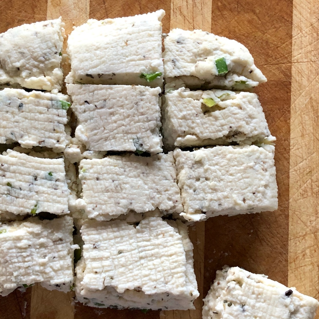 Garlic Herb Paneer, placed on a wooden cutting board and cut into cubes