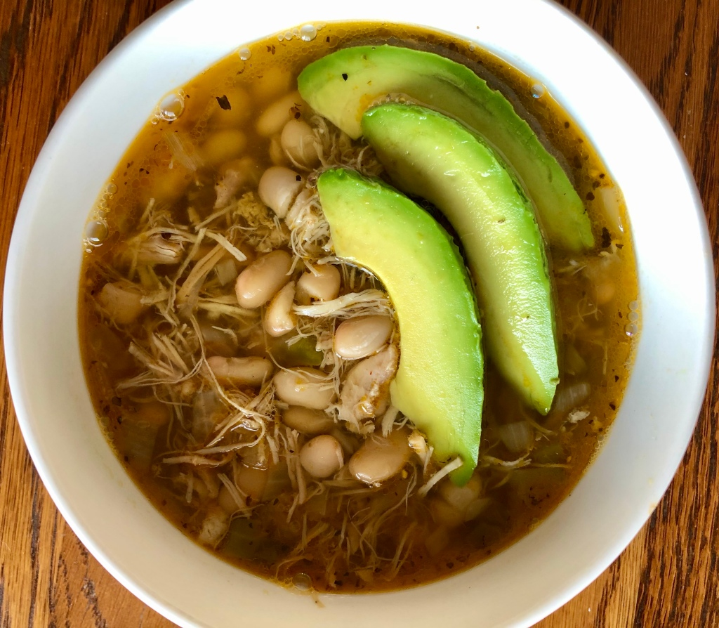 White Chicken Chili in a bowl, topped with three avocado slices