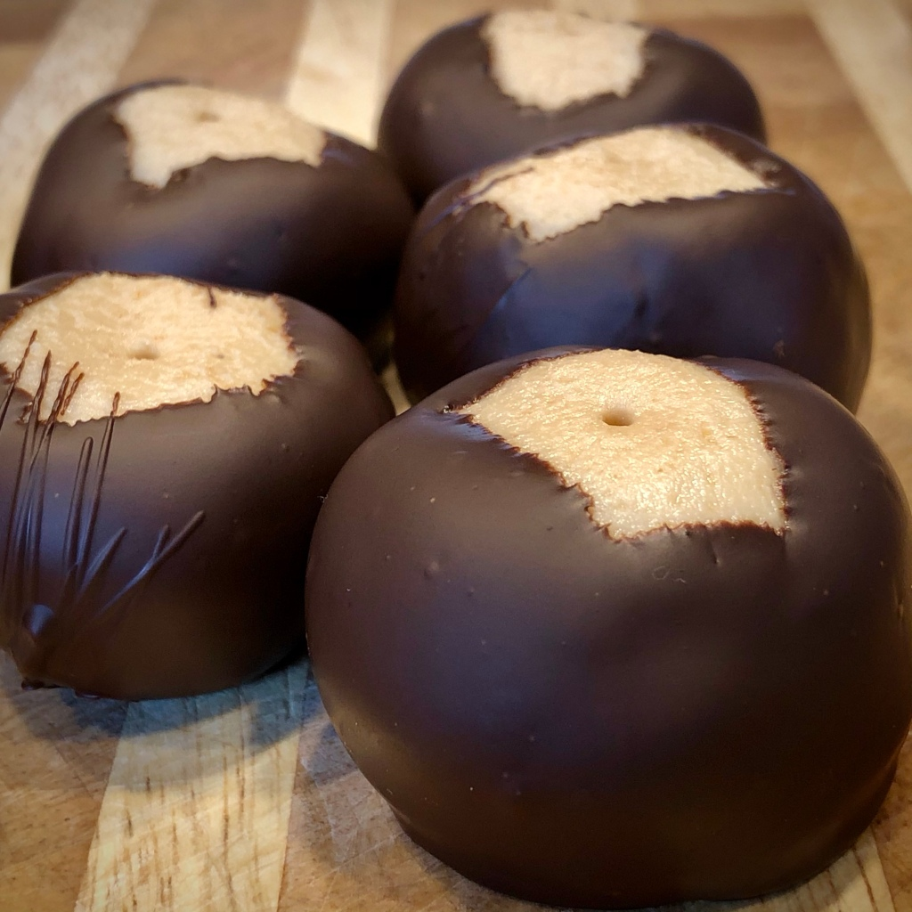 Five cashew butter buckeyes—light tan-colored fudgy candy dipped in dark chocolate   The tops are exposed, revealing the cashew butter candy underneath