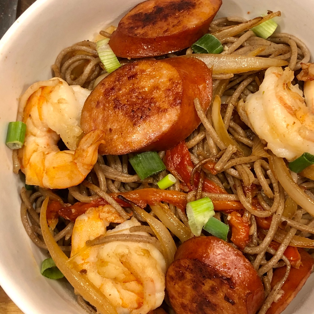 Soba noodles in a bowl, topped with shrimp, seared Andouille sausage, roasted red pepper, julienned yellow onion, and chopped green onions
