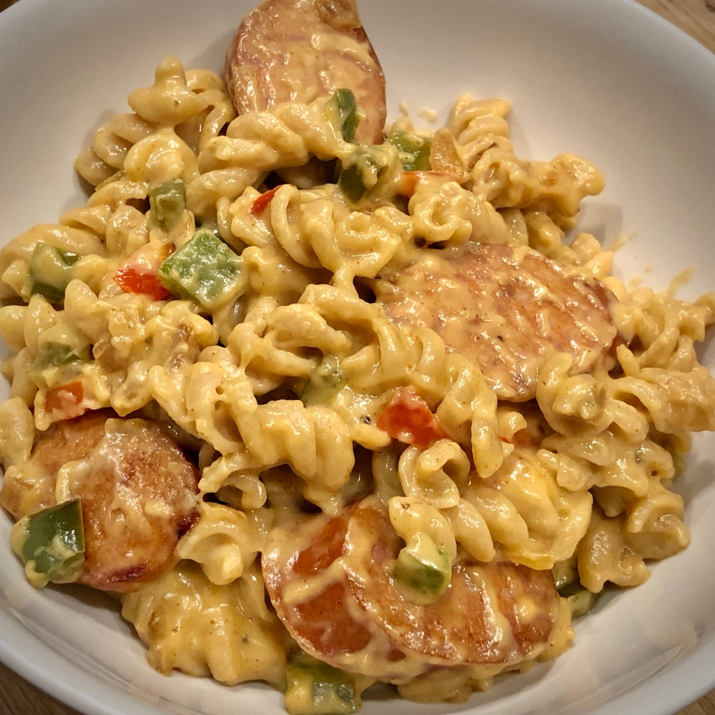 Rotini pasta mixed with diced red and green bell pepper and slices of sausage, covered in a cheese sauce and put in a bowl