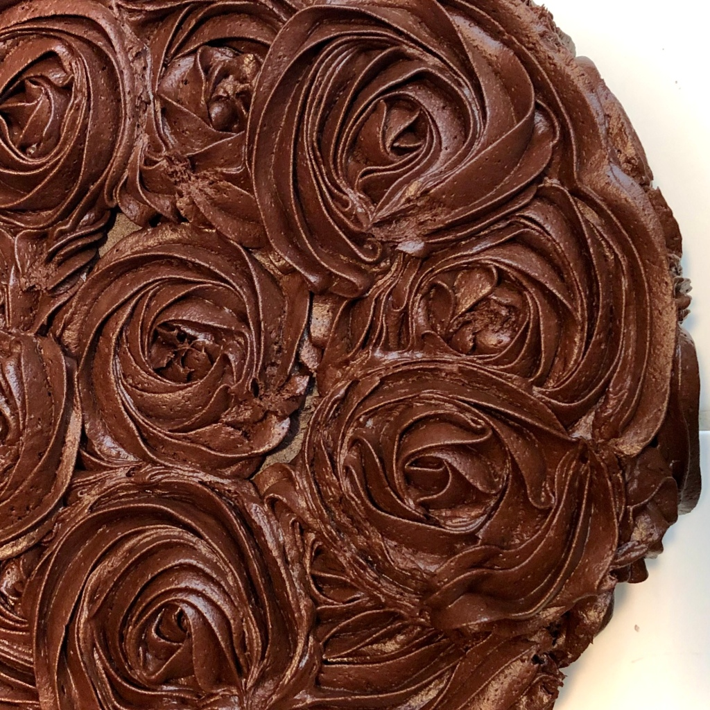 Decorator's Chocolate Frosting piped onto a cake in rosettes